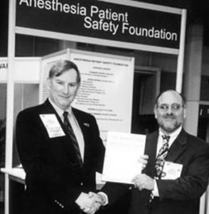 During the 2001 ASA Annual Meeting, at the APSF booth, John Eichhorn, MD (left), founding Newsletter Editor, turns over the page proofs and all good wishes to his successor Editor Robert Morell, MD.