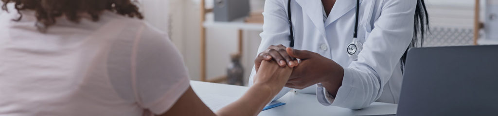 A doctor holds the hand of a patient