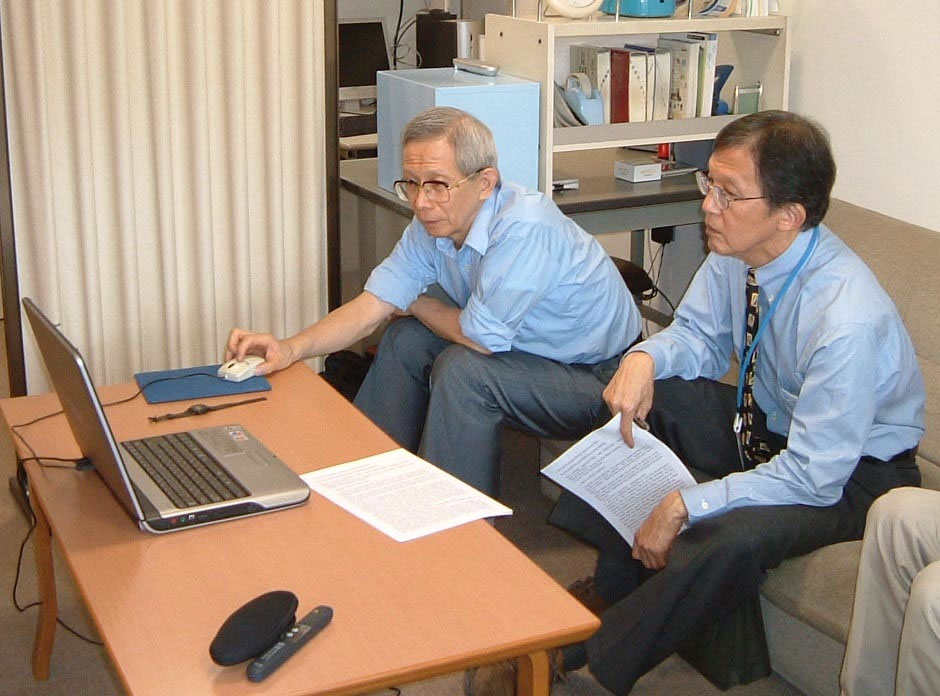Figure 5: Dr. Aoyagi showing his work to Dr. Byron Aoki of the University of Hawaii<br /> At the author's office,<br /> Head of the department of anesthesia and ICU<br /> National Center for Child Health and Development, 2002